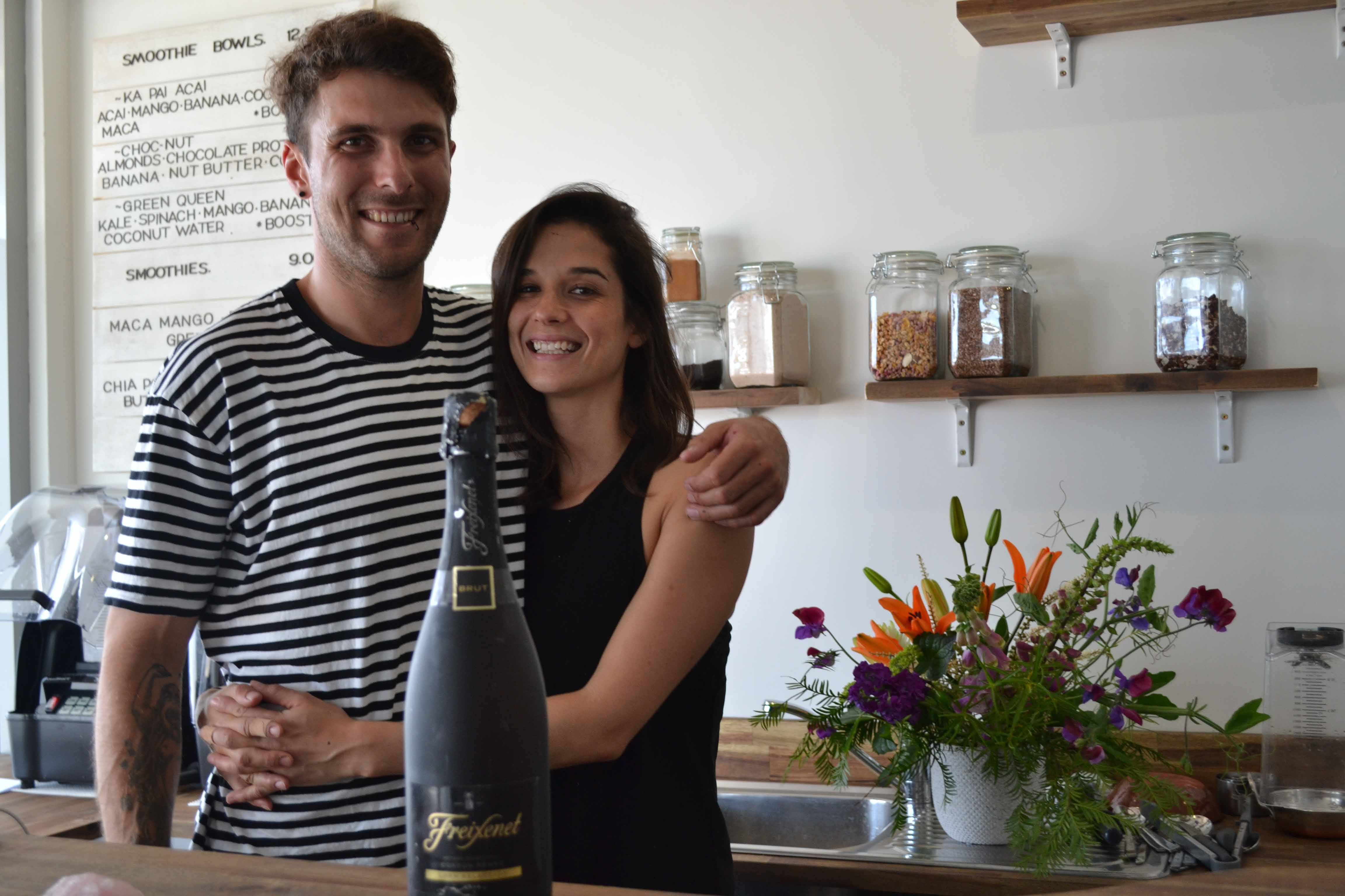 Raph and Eden at Lifted and ready to celebrate with a bottle of bubbly. Flowers courtesy of lessor Chris Leuthart.