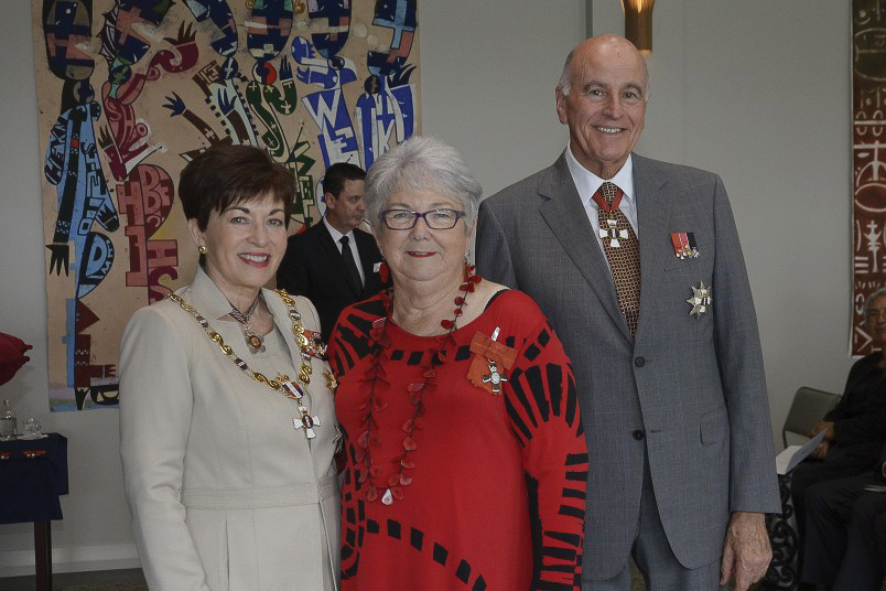 Christine proudly wears her MNZM lapel badge,    flanked by the Governor-General and her husband Sir David Gascoigne, at the investiture