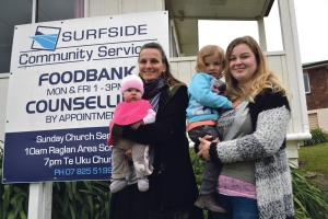 Sandra with baby Freia, left, and two-year-old Marnie held by au pair Soraja outside the foodbank from where the produce is distributed.