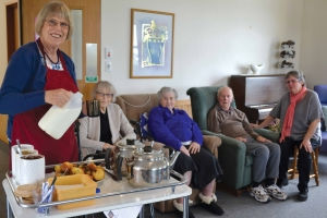 Kathleen serves morning tea. From left: Margaret Galloway, Helen Povey and Andy Galloway with Margaret looking on